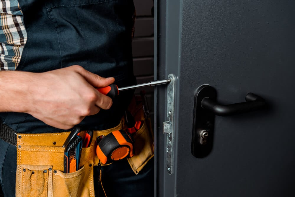 Cropped view of installer holding screwdriver near door handle   Big Easy Iron Works