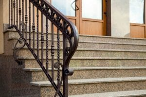 Detail of a house facade. New granite stairs with metal railings - Big Easy Iron Works